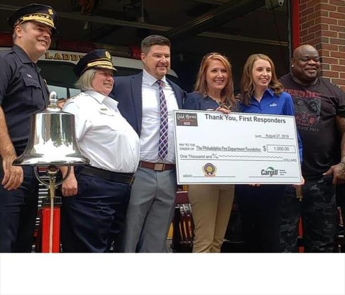 female accepting a donation check on behalf of The Philadelphia Fire Department Foundation